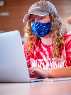 student using laptop in school of communiation and media wearing mask
