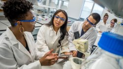 Three CELS students wearing lab safety glasses and coats talking in front of a microscope