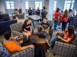 Students sitting around a Residence Hall common area hanging out.