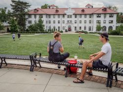 Two students sitting near the Freeman/Russ Quad enjoying a nice day.