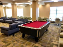 Another picture of the common area in Sinatra Hall featuring a pool table and some couches and chairs.