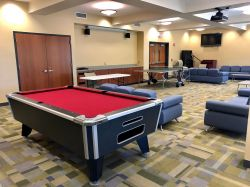 The common area in Sinatra Hall featuring some couches and chairs, a pool table and a television.