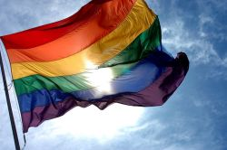 A rainbow flag flowing in the breeze on a bright and sunny day.