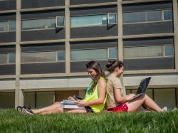 Two students sitting back to back outside of Blanton Hall in the grass.