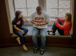 Three students sitting in a Residence Hall talking to one another.
