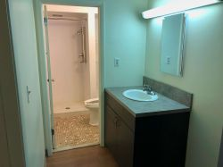 The bathroom at a Hawk Crossing's Apartment featuring a vanity and sink with a separate room for shower and toilet.