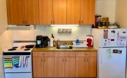 A view of the kitchen counter space, fridge and stove at a mult-floor Hawk Crossings apartment.