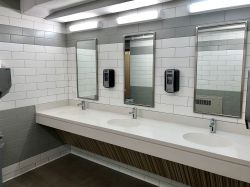 The bathroom in Stone Hall featuring three sinks and mirrors.