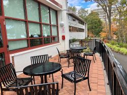 The outside patio of Stone Hall with table and chairs and a view of the New York skyline.