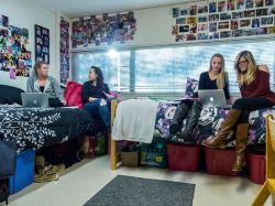 Four students sitting around a dorm room on their laptops and having conversations.