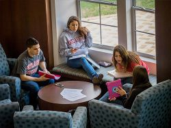 Students sitting around in a Residence Hall showing one-another things on an iPad and studying.