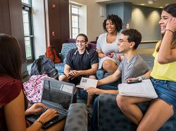 Students sitting around a Residence Hall studying and talking to one another.