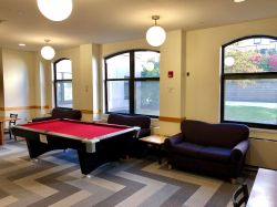 The common area in the Village Apartments with a pool table and some couches.