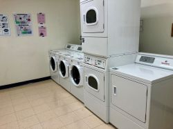 The laundry area in the Village Apartments with washers and driers.