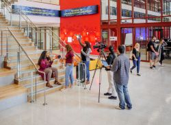 SCM students filming on lobby stairs