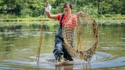 Photo of student wearing waders in river and holding large fishing net.