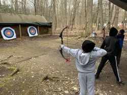 Students practice their bow and arrow skills during the Archery class