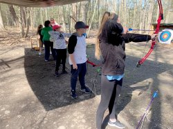 Students practice using a bow and arrow during the Archery class