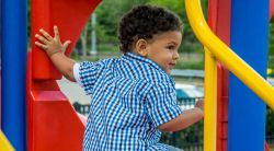 Image of a small child on a playground play structure ready go to down the slide.
