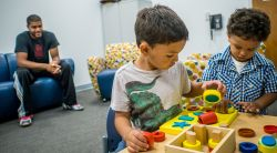 Image of children in a clinicial setting playing with blocks while parent looks on.