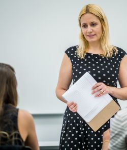Image of a faculty member, Svetlana Shpiegel, listening to a student talking in a classroom setting.