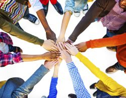 Photo of about 10 individuals in a circle with their hands together symbolizing teamwork.