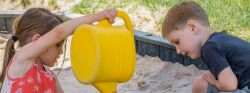 Image of two children playing in a sandbox. One is pouring sand from a watering can.