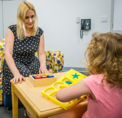 Image of a clinician interacting with a child with toys on the table.