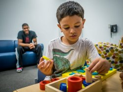 photo of young boy playing with blocks in foreground and an adult blurred in the background
