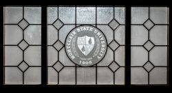 Decorative glass window with the Montclair State Shield on it.