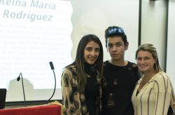 Photo of three students standing together at an event with a Cuban poet.