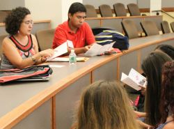 Photo of Prof. Maria Jose Garcia Vizcaino sitting and talking with students at an orientation session.