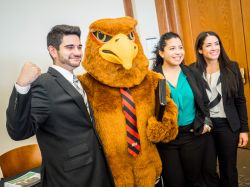Rocky the Red Hawk with students in business attire