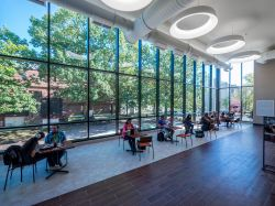 Students sitting in the dining area of the Student Center with giant windows.
