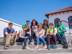 Students sitting on the steps on their phones.