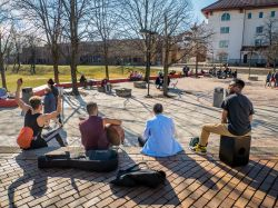 Students sitting in the Quad on a sunny day