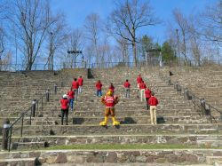 students and Rocky the Red Hawk standing in an M shape on the amphitheater steps