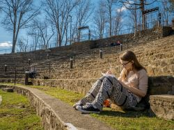 Student sitting on the steps of the Amphitheater writing in her notebook with other students in the background.