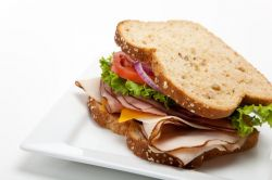 Turkey sandwich with cheese, lettuce, tomato and onion on wheat bread on a white plate