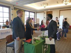 A student shaking hands with some recruiters at a career event. Everyone is smiling.