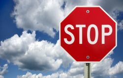 A stop sign against a blue, cloudy sky.