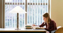 Girl studying at a table next to a window with a lamp.