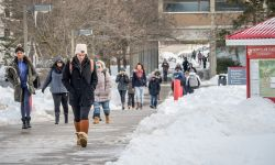 Students walking by Blanton and Webster Halls in the winter, snow beside the walkways.