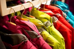 Pink, yellow, red and blue coats hanging on a rack.
