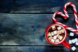 Picture of a blue and grey weathered table with a cup of hot chocolate with little marshmellows and two red and white candy candys positioned in the shape of a heart.
