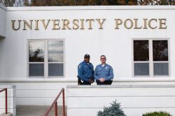 Two male university police men standing outside the station on a sunny day.
