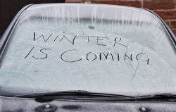 Picture of a car winter covered in ice and snow with the words Winter Is Coming written in the snow