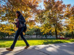 A student walking through campus by Calcia Hall and the Student Center Quad in the fall.