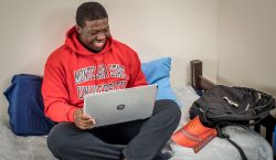 Picture of a student wearing a red Montclair State sweatshirt sitting on his bed looking at his laptop.