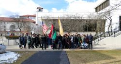 Large group of people standing outside the Student Center on a sunny day holding three flags in honor of Black Heritage Month